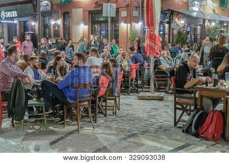 Thessaloniki, Greece - October 12 2019: Hellenic Nightlife Scene Of People At Outdoors Bar Restauran
