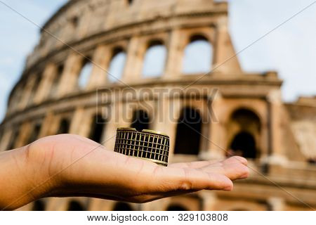 closeup of the hand of a caucasian man holding a miniature of the Flavian Amphitheatre or Colosseum, in Rome, Italy, in front of the famous landmark