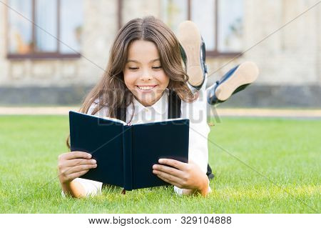 Knowledge Is More Than Information. Happy Small Girl Read Book On Green Grass. Adorable Little Schoo