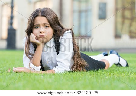Sad Without A Smile. Sad Schoolgirl Relax On Green Grass. Adorable Little Child With Sad Emotion On