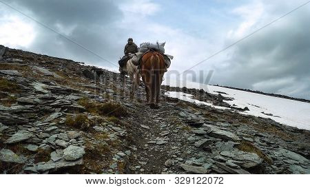 A Rider With Two Horses Climbing A Stone Path To The Top Of The Mountain On A Cloudy Day.