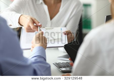 Focus On Woman Hand Holding Pen And Paper Folder With Important Documents. Businesswoman Giving Cont