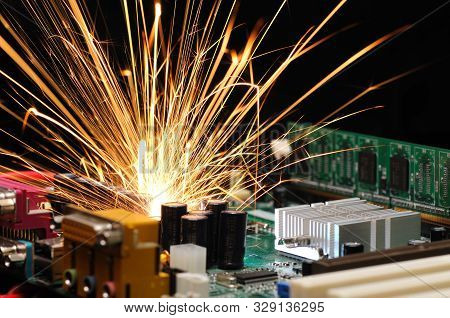Bright Burning Sparks Fly From The Chip Of Complex Electronic Equipment. Factory Breakdown Concept.