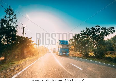 Truck In Motion On Country Road In Sunset Sun Sunshine Natural Sunlight. Tractor Unit, Prime Mover,