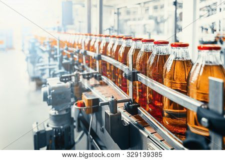Conveyor Belt, Juice In Glass Bottles On Beverage Plant Or Factory Interior, Industrial Manufacturin
