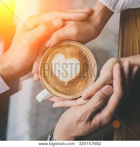 Valentine Day, Top View Of A Young Lovers Hand Holding A Heart Shaped Coffee Cup On A Wooden Table I