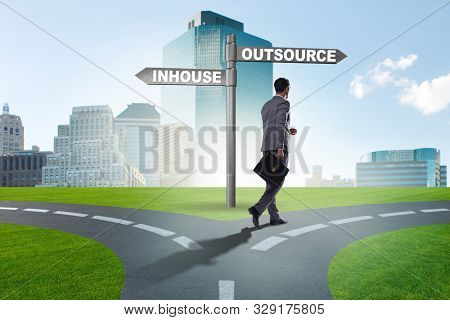 Businessman at crossroads deciding between outsourcing and inhou