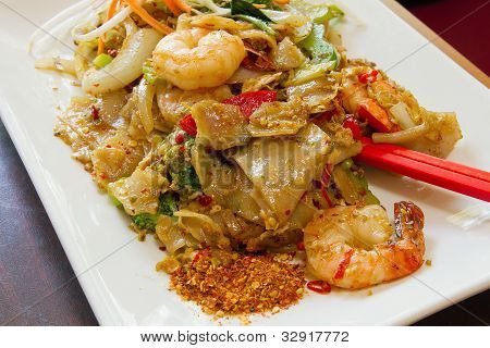Thai Pad Kee Mao Rice Noodle with Prawns and Vegetable Dish And Side of Spicy Chili Powder poster