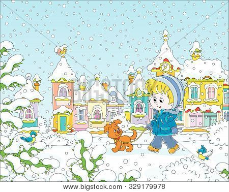 Little Boy Strolling With His Cheerful Pup Through A Snow-covered Park Of A Small Colorful Town On A