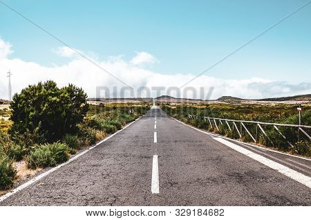 Empty Straight Road Surrounded By Dry Landscape. Pespective From The Middle Of The Road, Standing On