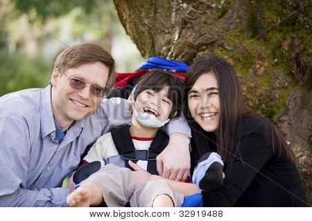 Disabled Boy In Wheelcahir Surrounded By Father And Sister