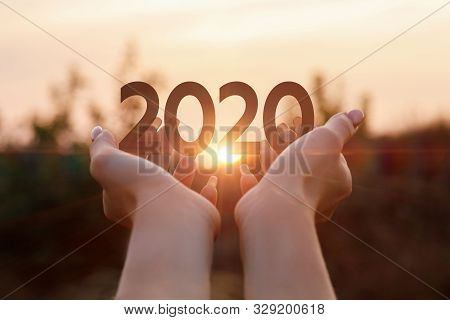 poster of The new concept 2020 year. The hands shows the numbers 2020 at sunset.