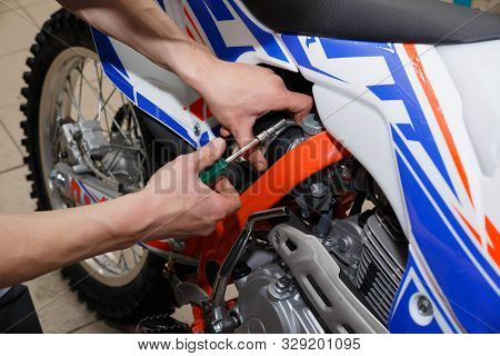 Motorcyclist Replaces, Checks The Glow Plug In A Motorcycle. Replacing The Spark In The Repair Shop.