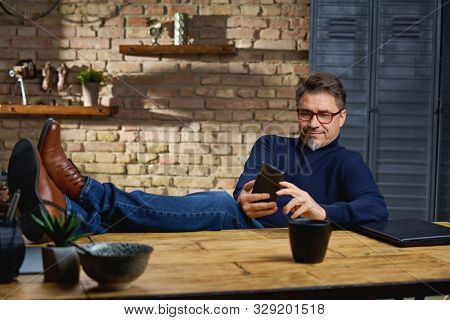 Older white man in glasses sitting at desk in dark room at home with feet on desk, working, using phone.