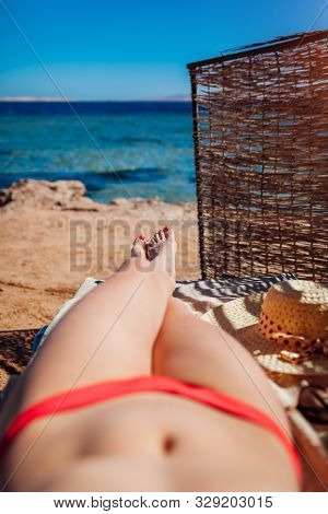 Woman In Bikini Relaxing On Beach Lying On Chaise-longue With Sea And Mountain View. Summer Vacation