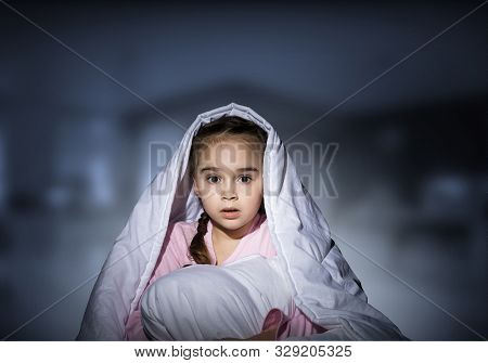 Scared Girl With Pillow Hiding Under Blanket. Startled Kid Lying In His Bed At Home. Little Girl Afr