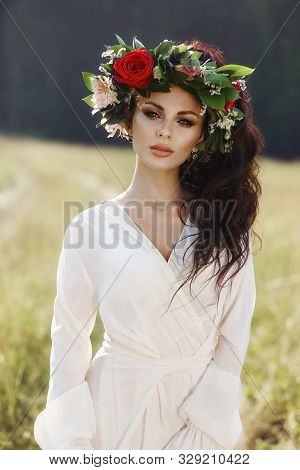 Girl In A Long Dress Stands In A Field With Wreath On Her Head And Bouquet Of Flowers In Her Hands,