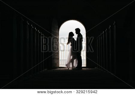 Silhouette Of Loving Couple Hugging While Standing In Doorway On Black Background, Bride And Groom I
