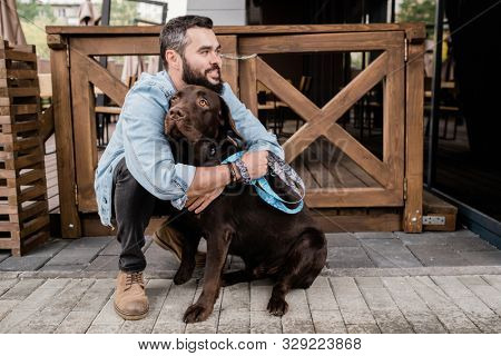 Happy young man in casualwear sitting on squats and embracing his cute brown purebred dog while chilling with him