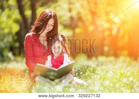 Happy mother and daughter read a book in summer park. Beauty nature scene with family outdoor lifestyle. Happy family resting together on green grass, cuddling and having fun outdoor