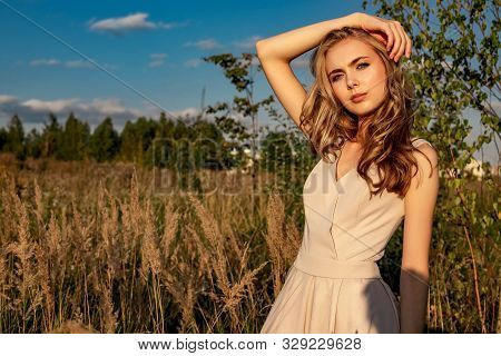 Portrait Of A Blond Girl In A Dress That Sits In A Field With Tall Grass And A Birch.