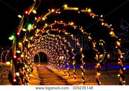 A Tunnel Of Brightly Illuminated Christmas Lights Crosses A Town Square On A Cold December Evening