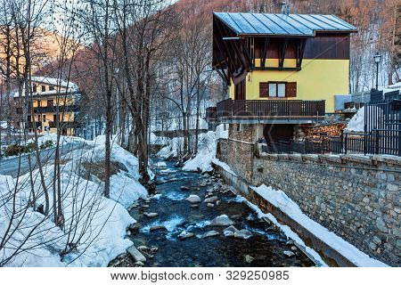 Mountain creek flows along a snowy shore and a wooden house in alpine resort of Limone Piemonte in Northern Italy.