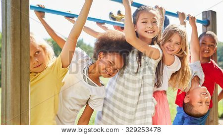 Multicultural kids as friends while doing gymnastics on a jungle gym