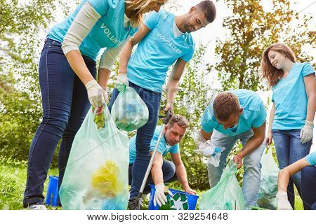 Group of volunteers as environmentalists collect garbage in nature