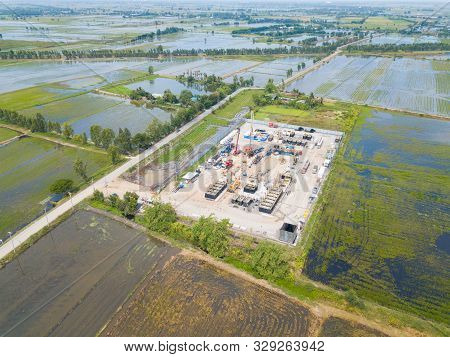 Oil And Gas A Land Rig, Onshore Drilling Rig, In The Middle Of A Rice Field Aerial View From A Drone