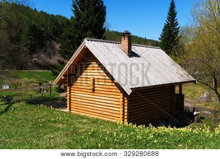 New Log-house Made By Old Technologies In A Green Meadow By The River. Beautiful Natural Background,