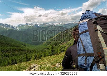 A Young Traveler With A Backpack Sitting And Looks At The Distance At A Beautiful Mountain Range.