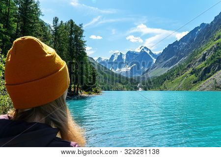 A Girl In A Knitted Hat On The Shore Of A Beautiful Lake, Looking At The Mountain Peaks. Focus On Th