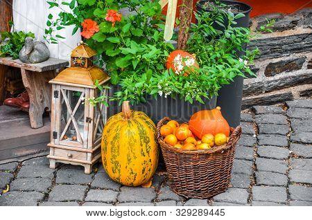 Beautiful Autumn Street Decoration. Wooden Lamp, Squash, Orange Pumpkins And Wicker Basket With Appl