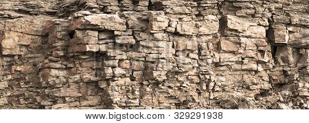 Rock Cliff Face Background. Toned. Wild Stone Protruding Crumbling Layered Blocks In Quarry. Abstrac