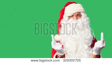 Middle age handsome man wearing Santa Claus costume and beard standing Showing middle finger doing fuck you bad expression, provocation and rude attitude. Screaming excited poster
