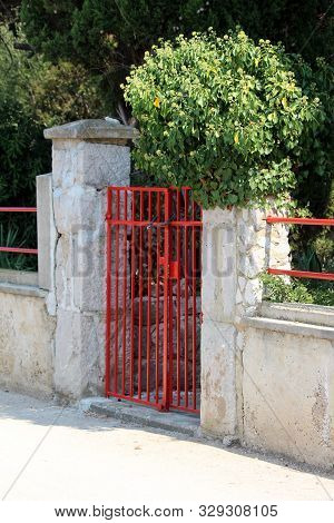 Locked Front Yard Red Metal Entrance Doors Mounted On Dilapidated Stone And Concrete Fence Pole Surr