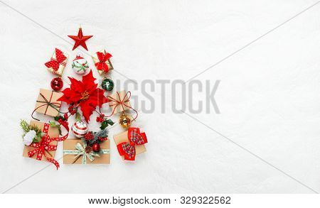 Christmas tree made from Christmas gifts and decorations on white background. Creative winter holiday concept. Flat lay.