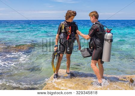 Two Young Divers Checking Their Diving Equipment In Sea Of Bonaire