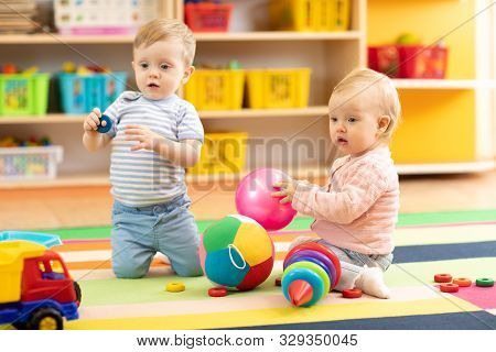 Babies Boy And Girl Playing On Floor With Toys. Children Toddlers In Creche Or Nursery