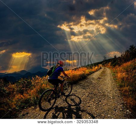 Cycling in mountain woman on cycle gravel road in autumn forest. Mountain biking in autumn landscape forest. Woman cycling MTB flow uphill trail.