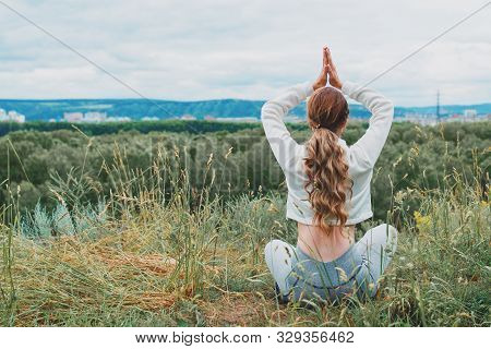 Meditation Outside The City In Nature. Young Woman Meditating Sitting On The Ground. There Is A Plac