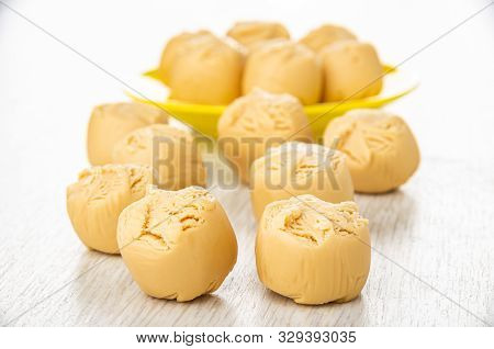 Many Creamy Fudge On Light Wooden Table, Fudge In Yellow Saucer