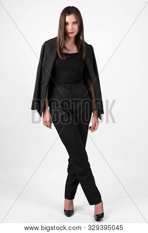 Young Beautiful Girl In Black Pantsuit On White Background Full Length, Long Dark Straight Hair, Bea