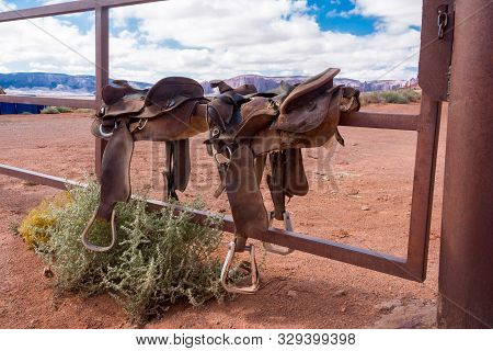 Two Western Saddles Sitting On The Gate Of A Metal Fence.