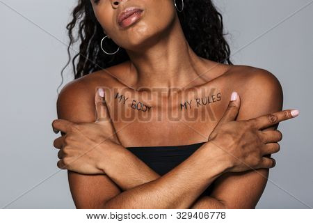 Cropped image of a beautiful african woman isolated over grey wall background with my body my rules inscriptions on clavicles.
