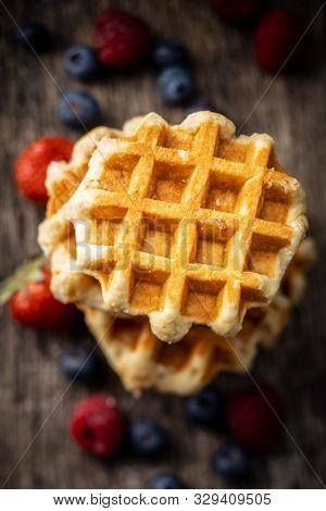 Waffles with blueberries and raspberries on old wooden table.