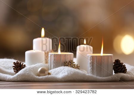 Composition With Candles In Ornate Holder On Wooden Table Against Blurred Background. Christmas Deco