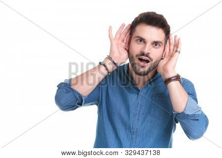 Clumsy casual man making a funny face and holding his hand behind his ears while wearing a blue shirt and standing on white studio background