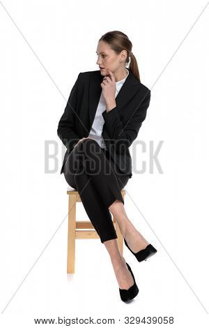 lovely businesswoman wearing black suit sitting with crossed legs and looking aside intrigued against white studio background